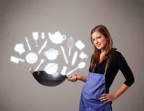 Молодая женщина с иконами вспомогательного оборудования кухни Стоковое Фото