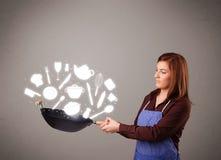 Молодая женщина с иконами вспомогательного оборудования кухни Стоковое фото RF