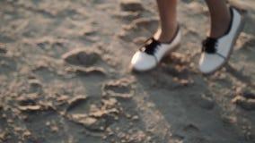Молодая женщина с длинными волосами одела в прозрачной тунике представляя на заходе солнца на пляже видеоматериал