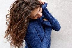 Молодая женщина с длинными волосами усмехаясь против серой стены стоковые изображения