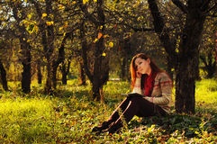 Молодая женщина с длинным красным чтением волос под деревом Стоковые Изображения