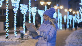 Молодая женщина с картой ищет правильное направление в ноче зимы акции видеоматериалы
