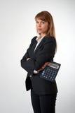 Молодая женщина с калькулятором в ее руке Стоковое Изображение