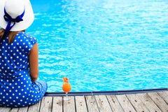 Молодая женщина с коктеилем около бассейна Стоковая Фотография RF