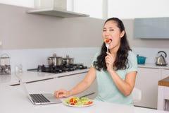 Молодая женщина с компьтер-книжкой есть салат в кухне Стоковая Фотография RF