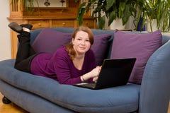 Молодая женщина с компьтер-книжкой на софе Стоковое Изображение