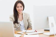 Молодая женщина с компьютерами на столе в офисе Стоковые Фотографии RF