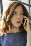 Молодая женщина с красивыми голубыми глазами говоря на сотовом телефоне стоковая фотография rf