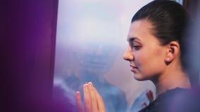 Молодая женщина с красивым стиля причёсок snuggle элегантно к окну ждать тоскливость Теплые тени акции видеоматериалы