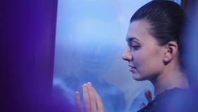 Молодая женщина с красивым snuggle стиля причёсок к панорамному окну ждать тоскливость Холодные тени акции видеоматериалы