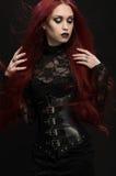 Молодая женщина с красными волосами в черном готическом костюме стоковое фото rf