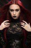 Молодая женщина с красными волосами в черном готическом костюме стоковое фото