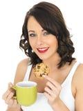 Молодая женщина с кружкой чая и печенья Стоковое Фото