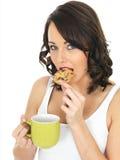 Молодая женщина с кружкой чая и печенья Стоковые Изображения RF