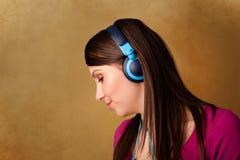 Молодая женщина с наушниками слушая к музыке с космосом экземпляра Стоковые Фото