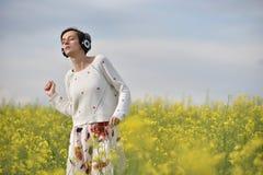 Молодая женщина с наушниками стоковое изображение rf