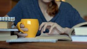 Молодая женщина с оранжевой чашкой читает книгу на таблице сток-видео