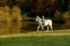 Молодая женщина с лошадью в озере стоковые фото