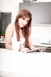 Молодая женщина с ПК таблетки в кухне Стоковые Фото