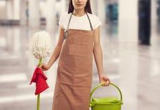 Молодая женщина с поставками чистки в здании Стоковое Изображение