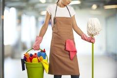 Молодая женщина с поставками чистки в здании Стоковые Изображения
