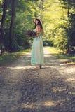Молодая женщина с полевыми цветками на проселочной дороге Стоковое фото RF