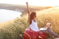 Молодая женщина с поднятой рукой выигрывает приз Стоковое Фото