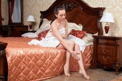Молодая женщина с полотенцем в спальне Стоковые Изображения