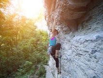 Молодая женщина с подъемами веревочки на утесе Стоковое Фото