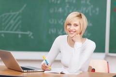 Молодая женщина с примечаниями сочинительства компьтер-книжки на столе Стоковое фото RF