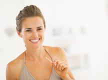 Молодая женщина с пробиркой хлопка в ванной комнате Стоковые Изображения RF