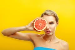 Молодая женщина с плодоовощами на яркой оранжевой предпосылке Стоковое Изображение RF