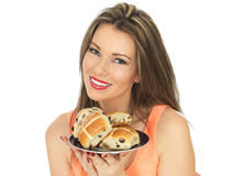 Молодая женщина с плюшками пасхи горячими перекрестными Стоковое фото RF