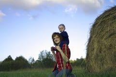 Молодая женщина с ребёнком на плечах Стоковое фото RF