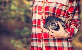 Молодая женщина с ретро камерой фото и рубашка шотландки внешняя стоковое изображение rf