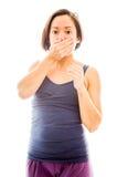 Молодая женщина с рукой над ее ртом и ударом Стоковые Фотографии RF