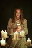 Молодая женщина с свечой в руке стоковые фотографии rf