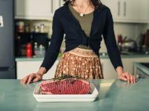 Молодая женщина с соединением жарки в кухне стоковые фото