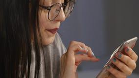 Молодая женщина с стеклами просматривая фото на smartphone Отраженный в стеклах видеоматериал