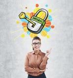 Молодая женщина с стеклами указывая на ключ успеха Стоковое фото RF