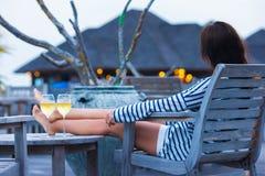 Молодая женщина с стеклом белого вина на вечере стоковая фотография