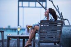 Молодая женщина с стеклом белого вина на вечере стоковая фотография rf