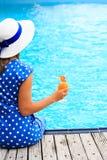 Молодая женщина с стеклом коктеиля около бассейна Стоковые Изображения