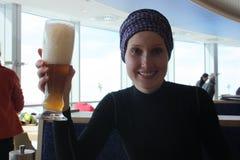 Молодая женщина с стеклом пива в ресторане Стоковые Изображения