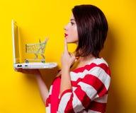 Молодая женщина с тележкой и компьтер-книжкой стоковое фото