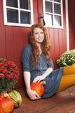 Молодая женщина с тыквой перед домом сада стоковые фото