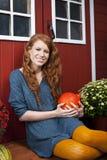 Молодая женщина с тыквой перед домом сада стоковое изображение