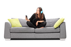Молодая женщина слушая к музыке на ее телефоне Стоковые Изображения RF