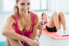 Молодая женщина слушая к музыке на спортзале Стоковое фото RF