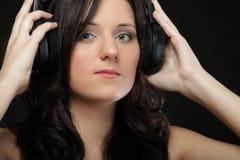 Молодая женщина слушая к музыке на шлемофоне Стоковые Фото